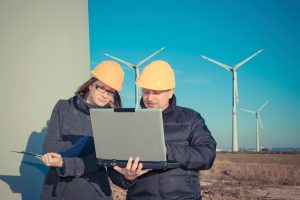 stock workers out in the field with wind turbines