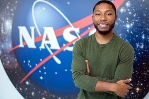Engineering Management alumni Kenneth Harris II in front of the NASA logo